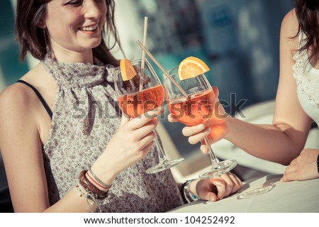 Two Young Women Cheering with Cold Drinks - stock photo