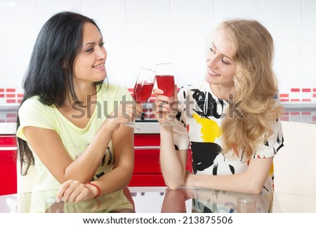 Two young women clinking glasses - stock photo