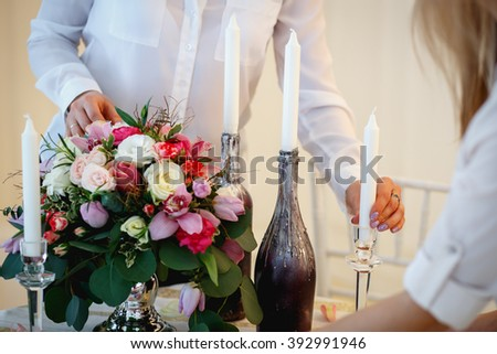 Two young women create a decoration. Decor and floral composition on a table.