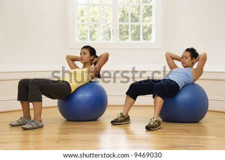 Two young women doing ab workout on balance balls. - stock photo