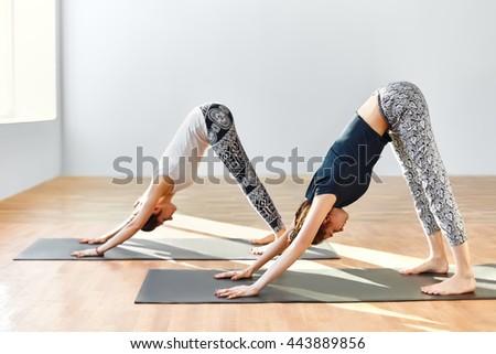 Two young women doing yoga asana Downward Facing Dog. Adho Mukha Shvanasana - stock photo
