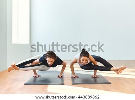 Two young women doing yoga asana eight-angle pose. Astavakrasana - stock photo