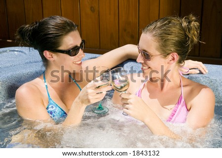 Two young women drinking wine in a Jacuzzi