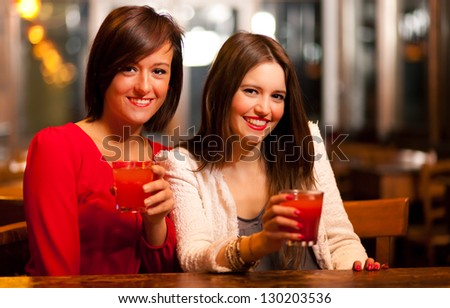 Two young women enjoying a drink in a pub - stock photo