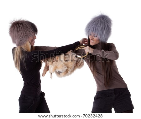 Two young women fighting for magnificent fur's bag on a white background. Sale. - stock photo