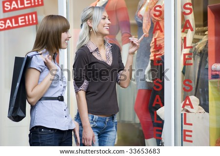 two young women friends looking at a window shop during the sale - stock photo