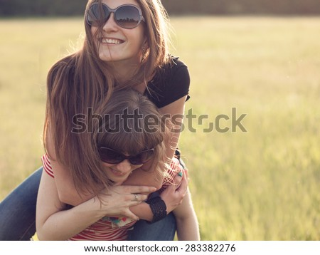Two young women have fun outdoors. The best friends - stock photo