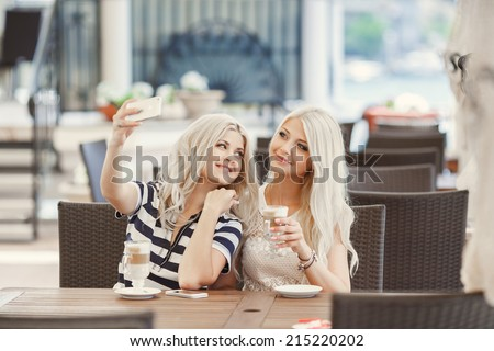 Two young women having coffee break together. Two women using a smart phone - stock photo