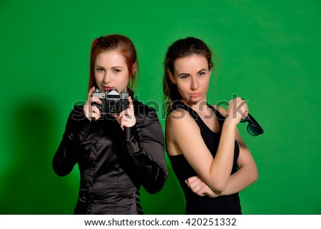 Two young women having fun posing and making photos with old cam