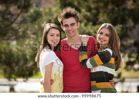 two young women holding a young man