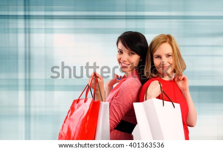 Two young women holding shopping bags - stock photo