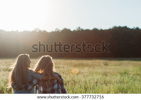 Two young women hugging at sunset.  Back view. Best friends - stock photo
