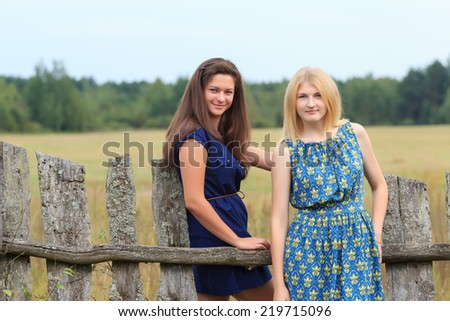 Two young women in dresses in an countryside - stock photo
