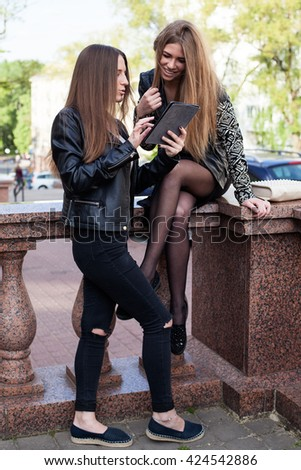 Two young women in the city are looking at the screen of a tablet and smiling