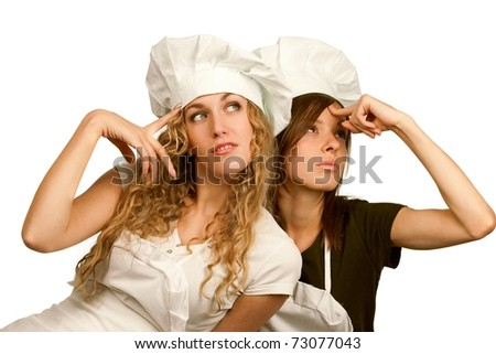 "Two young women in white chef dress think: ""what to cook?"""