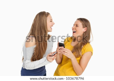 Two young women laughing while holding their cellphones against white background - stock photo