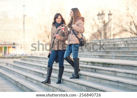 Two young women leaving office building - stock photo