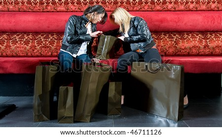 Two young women looking at their newly bought articles while taking a rest on a couch. - stock photo