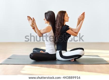 Two young women meditating in Lotus Pose. Padmasana - stock photo