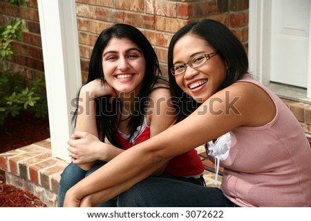 Two young women (middle eastern and chinese indonesian) sitting outside home. - stock photo