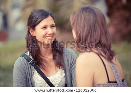 Two Young Women on a Bench at Park - stock photo
