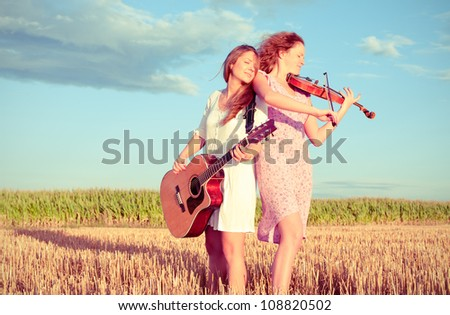 Two young women playing guitar and violin outdoors on the field in summer evening. Split toning. - stock photo