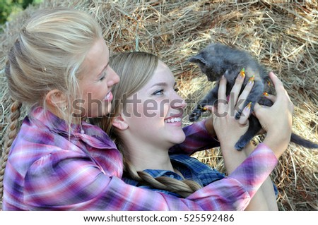 two young women playing with funny kitten in the ranch