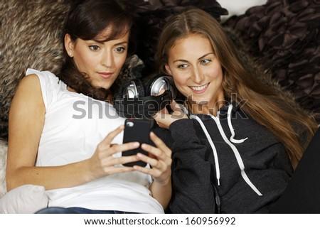 Two young women relaxing and listening to music at home