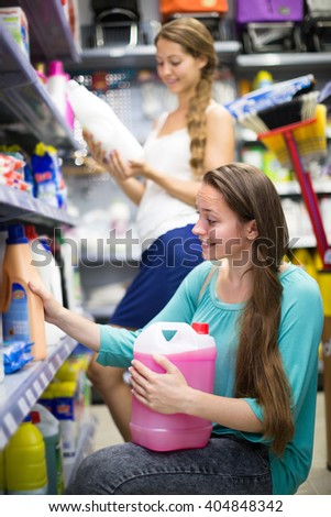 Two young women selecting detergents at the household store