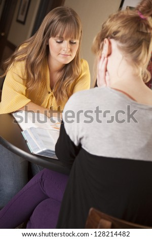 Two young women sit and study the bible together. - stock photo