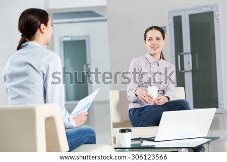 Two young women sitting at office having conversation