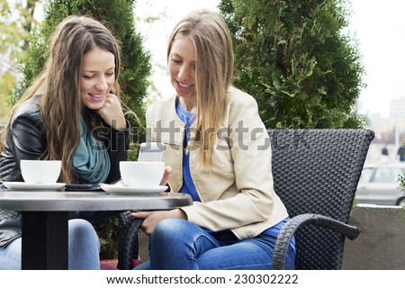 Two young women sitting in cafe and using a smart phone outdoors. - stock photo