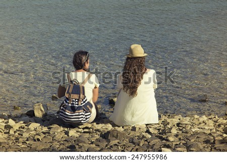 Two young women sitting on the beach together - stock photo