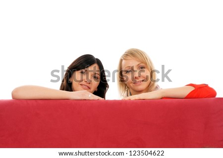 Two young women sitting on the couch / two girlfriends - stock photo