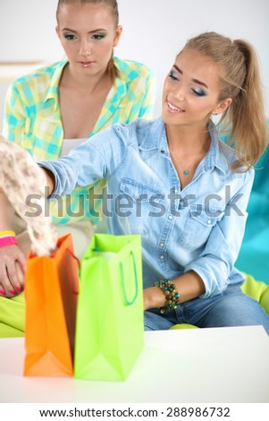 Two young women sitting with laptop  and credit cart - stock photo
