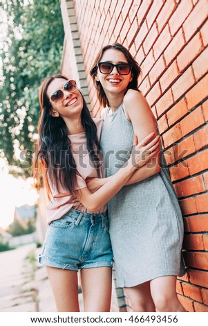 Two young women smiling and stand near the brick wall. Best friends
