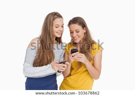 Two young women smiling while looking their cellphones against white background - stock photo