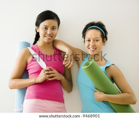 Two young women standing in workout clothes holding yoga mats and smiling. - stock photo