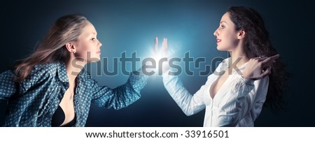 Two young women stretching hands. On dark background with flash effect.