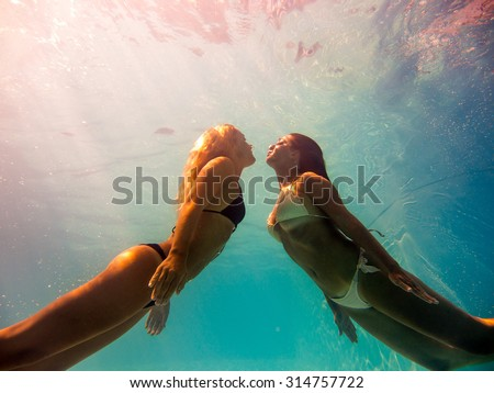 Two Young women swimming underwater in the swimming pool - stock photo