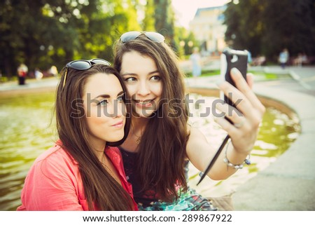 Two young women taking a selfie outdoors in summer