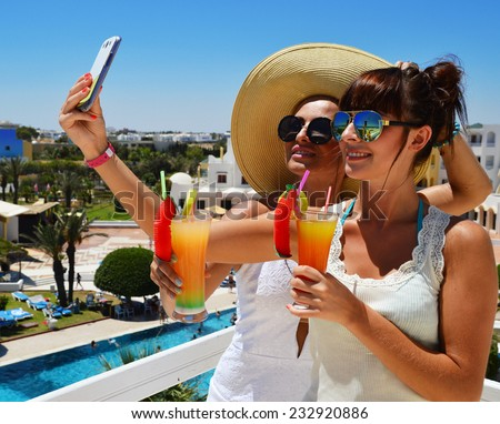 Two young women taking picture of themselves on vacation. Selfie - stock photo