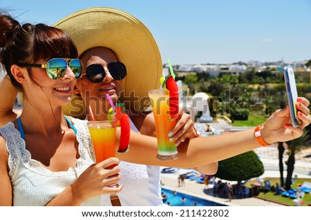 Two young women taking picture of themselves on vacation. Selfie on holiday - stock photo