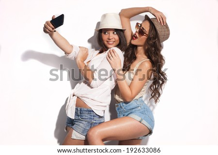 two young women taking selfie with mobile phone  - stock photo