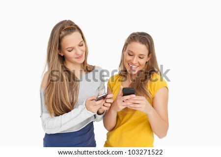 Two young women texting on their cellphones against white background - stock photo