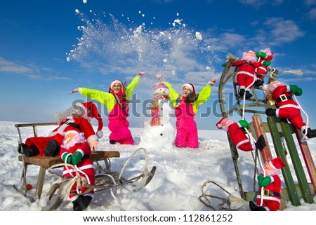 Two young women throwing snow on blue sky and sculpting snowman in street in wintertime