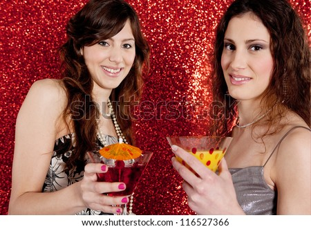 Two young women toasting and drinking cocktails while celebrating in front of a red glitter background. - stock photo