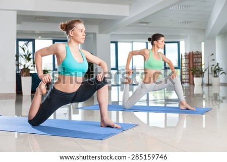 Two young women training in yoga exercise at the gym - stock photo