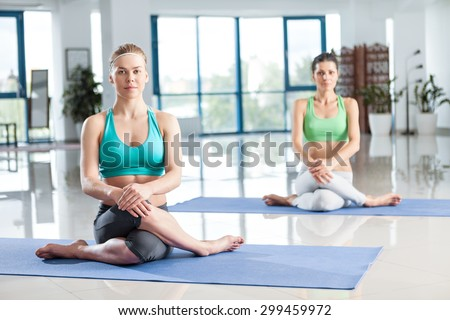 Two young women training yoga in the gym - stock photo