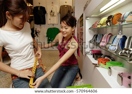 Two young women trying on belts in shop